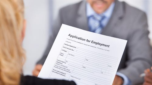 woman giving application for employment to man
