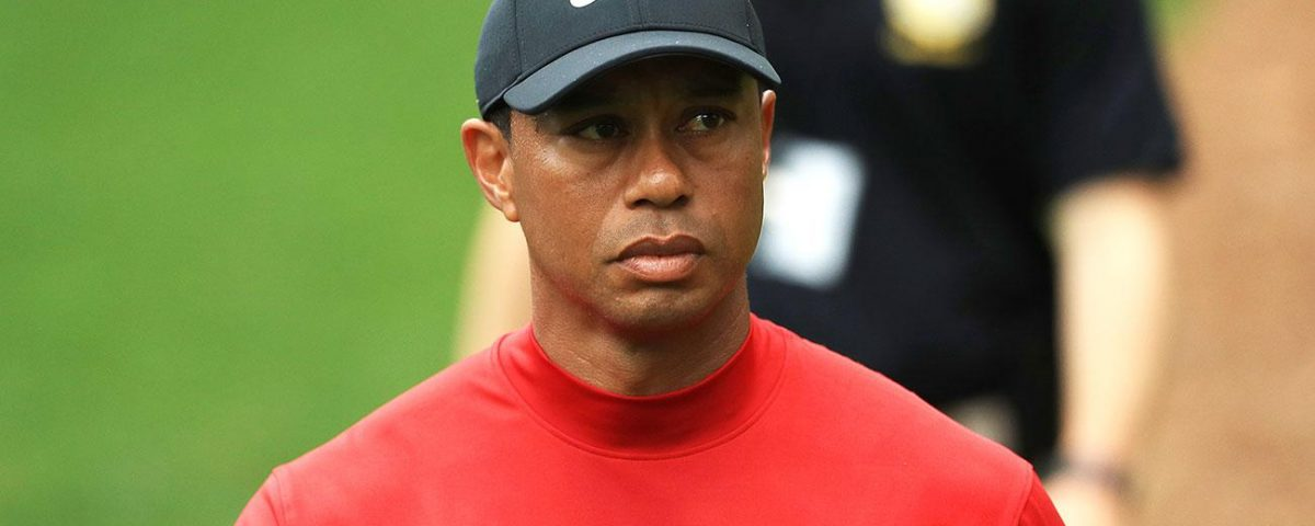 tiger woods in a black hat and red shirt